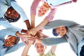 youth in a circle with hands in the center